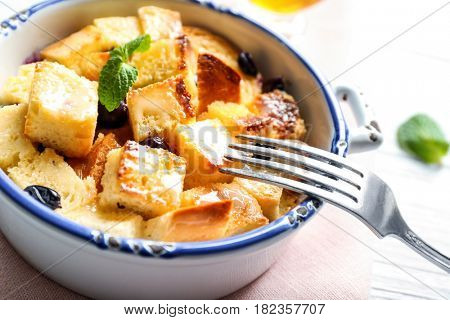 Bowl with delicious bread pudding on napkin, closeup