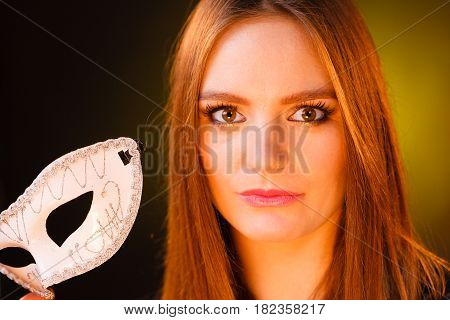 Party time holidays people and celebration concept. Woman long hair holds carnival white mask close up