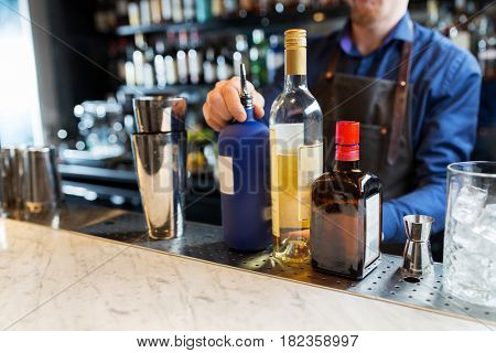 alcohol drinks, people and luxury concept - barman with shaker, bottles and jigger preparing cocktail at bar