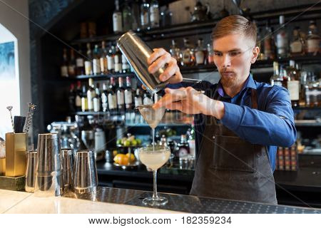 alcohol drinks, people and luxury concept - barman pouring cocktail from shaker through strainer into glass at bar