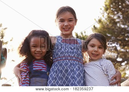 Portrait Of Three Girls Playing Outdoors At Home In Garden