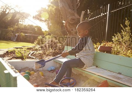 Boy Playing In Sand Box Outdoors In Garden