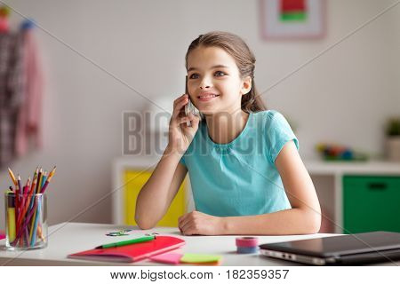 children, technology and communication concept - happy smiling girl distracting from homework and calling on smartphone at home