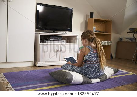 Girl Watches Television And Using Digital Tablet In Playroom