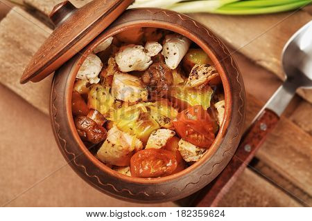 Crock pot with chicken ragout on wooden board