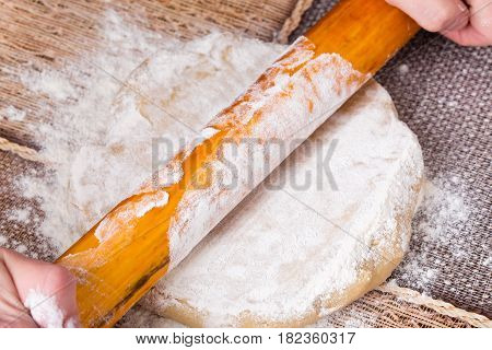 Flattening dough with rolling pin. Macro. Photo can be used as a whole background.