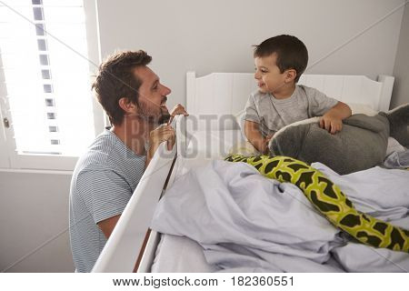 Father Saying Goodnight To Son At Bedtime