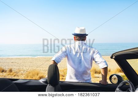 Man on the summer beach near car looking to the sea. Travel and summer vacation concept