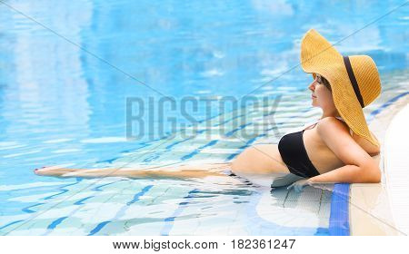 Pretty young pregnant woman relaxing in the swimming pool