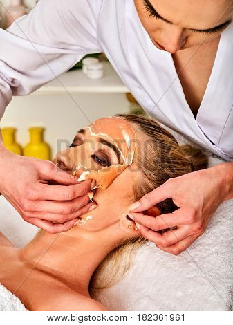 Collagen face mask . Facial skin treatment. Face of woman receiving cosmetic procedure in beauty salon close up number one isolated. Beautician removes mask.