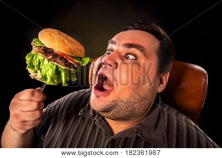 Diet failure of fat man eating fast food hamberger. Happy overweight person with wide-open mouth who spoiled healthy food by greedily eating huge hamburger on fork. Junk meal leads to obesity.
