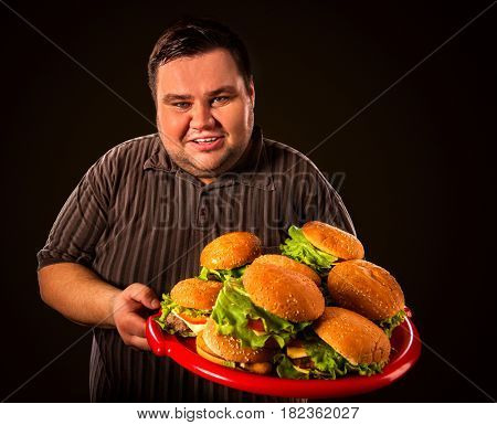Fat man eating fast food hamberger and carries treat for friends on tray. Breakfast for overweight person. Junk meal leads to obesity. Person regularly overeats concept on black background.
