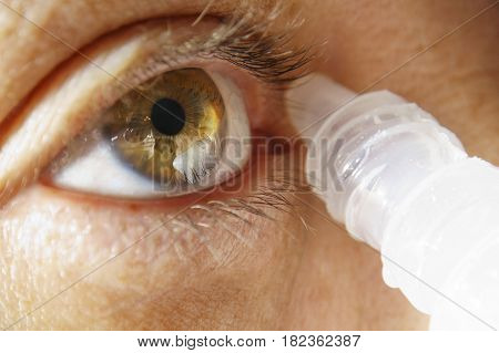 Woman macro brown eye applying eye drops