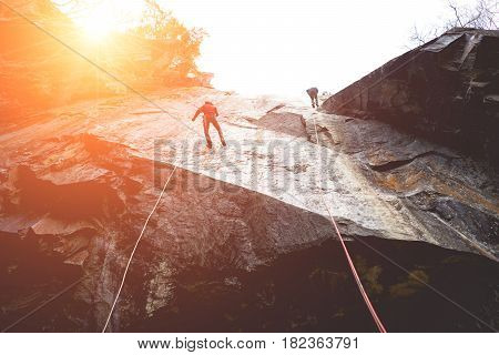 Climbers to conquer the rock. Climber go down the rope down