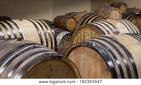 Old oak barrels in the cellar. Alcohol aging