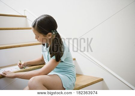 Girl coloring on stairs