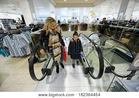 ENSCHEDE THE NETHERLANDS - APRIL 13 2017: A mother and child on the moving staircase in clothes store C&A after it has been reopened.