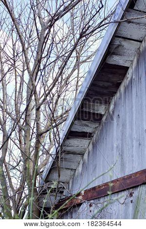Old rural country barn eave, with missing boards