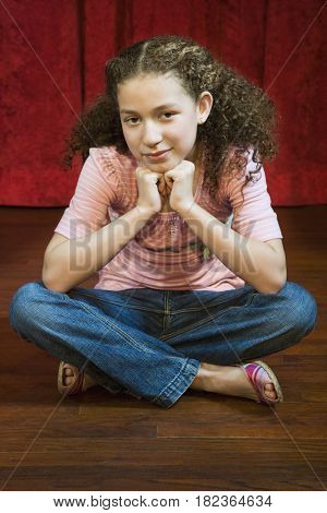 Mixed race girl sitting cross-legged on stage