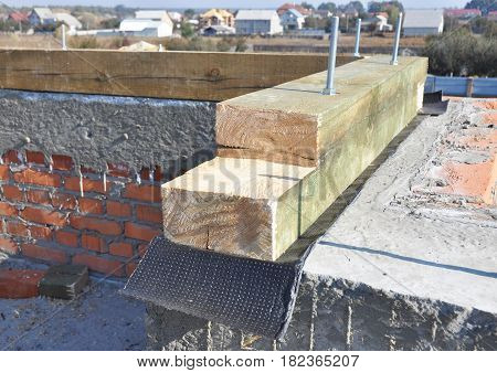 Roof wooden beams trusses installation with bitumen membrane on brick house wall. Roofing Construction Closeup.