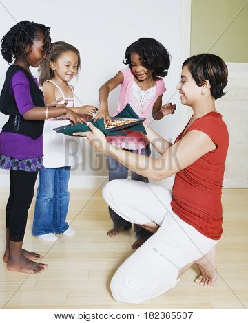 Woman serving cookies to girls