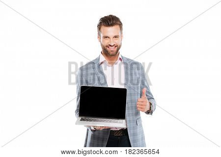 Image of cheerful young man standing isolated over white background and holding laptop computer. Looking at camera showing thumbs up.