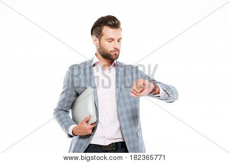 Picture of serious young man standing isolated over white background and holding laptop computer. Looking at watch.