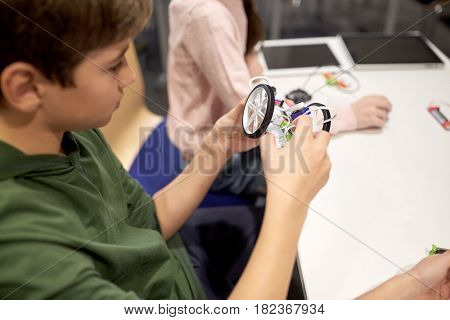 education, children, technology, science and people concept - boy building robot at robotics school lesson