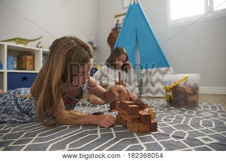 Two Girls Playing With Building Blocks In Bedroom