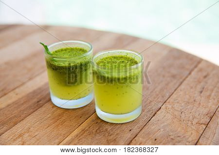 food and drinks concept - two glasses with fresh juice or mohito cocktails on bar table