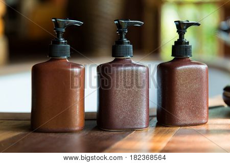 beauty, spa, luxury and bodycare concept - set of bottles with liquid soap or body lotion set at hotel spa bathroom