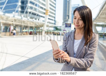 Business woman sending sms on mobile phone in bangkok city