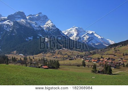 Village Gsteig bei Gstaad in Spring. Green meadow and snow capped mountains Schlauchhorn and Oldenhorn. Landscape in the Bernese Oberland Switzerland.