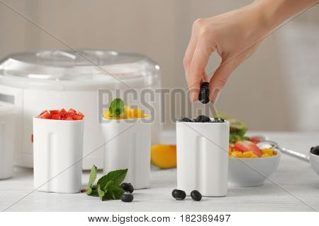 Hand of woman preparing tasty homemade yogurt in kitchen