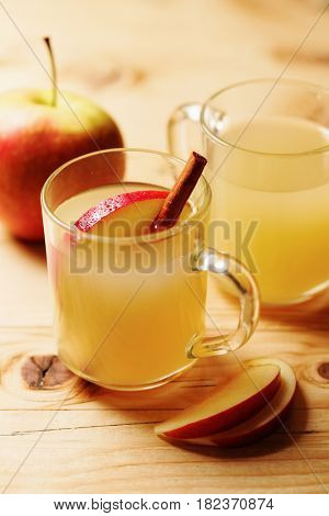 Homemade apple cider in a glass cup with cinnamon and an apple slice on wooden table