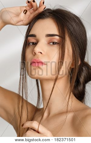 Amazing naked woman after spa procedures. Posing on grey background with hand on head.