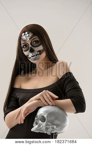 Woman with smart artistic makeup in horror style posing with silver skull in studio in her hands