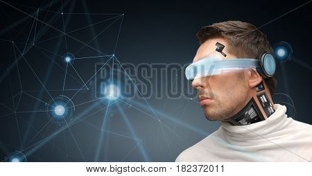 augmented reality, technology, business, future and people concept - man in virtual glasses and microchip implant or sensors over dark gray background looking at low poly network projection