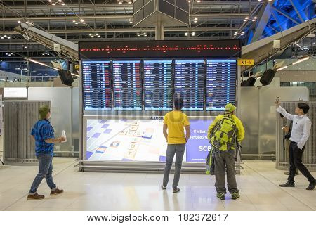BANGKOK, THAILAND - MARCH 8, 2017: Travellers checking departures at Suvarnabhumi Airport in Bangkok. This is one of the busiest airports in the world.