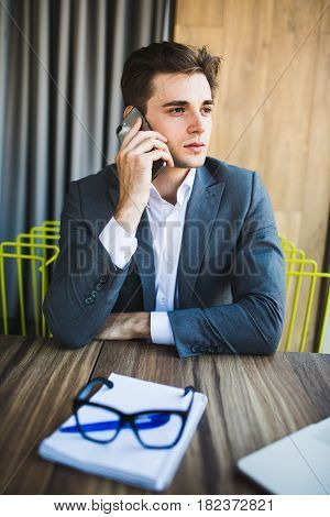 Young Businessman Caucasian In His Office On Phone In Front Notebook