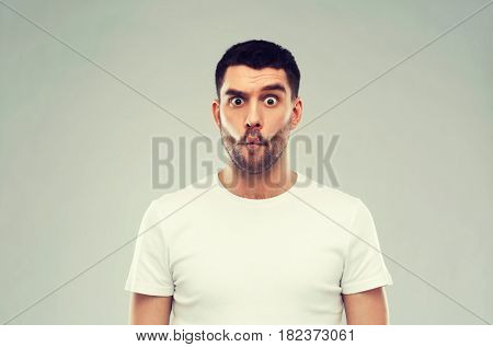 expression, fun and people concept - man with funny fish-face over gray background