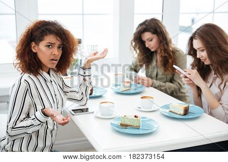 Side view of a displeased african woman sitting by the table in cafe near two friends which using smartphones