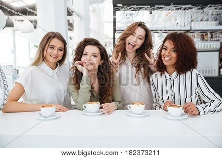 Four happy friends sitting by the table in cafe and looking at the camera