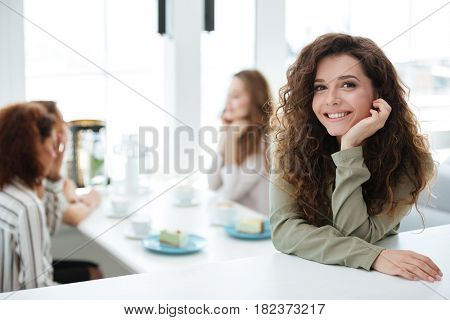 Pretty woman standing by the table in cafe with her friends on background