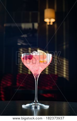 Barman at work, preparing cocktails. pouring cosmopolitan to cocktail glass. concept about service and beverages.