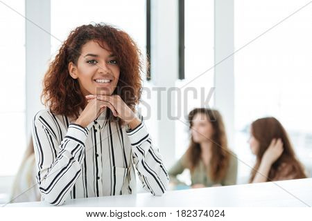 African woman standing by the table in cafe with her friends on background