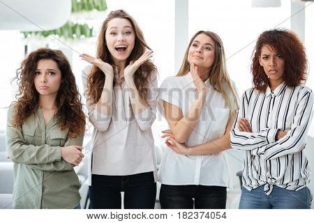 Four young pretty women standing and posing in cafe