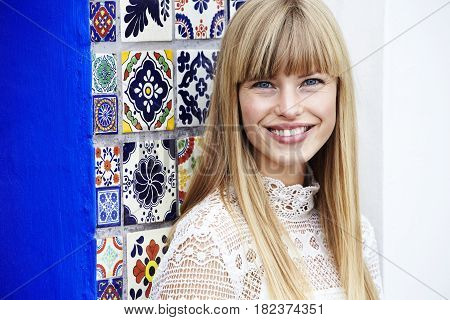 Beauteous young blond lady smiling with colourful background