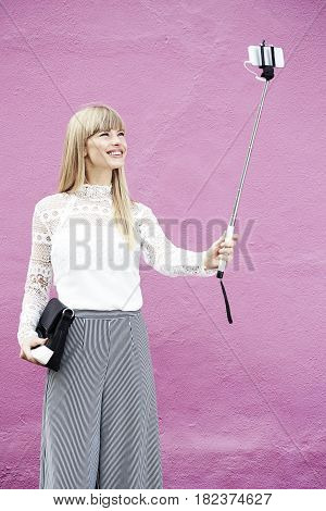 Stylish young blond woman posing for selfie