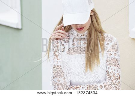 Young blond woman in white fashion looking down